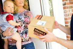 Consegna: L'uomo consegna il pacchetto fragile Fotografie Stock