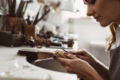 Conseguí mi inspiración Vista lateral de un joyero emocionado de sexo femenino que crea un anillo de plata en su banco de trabajo imagen de archivo libre de regalías