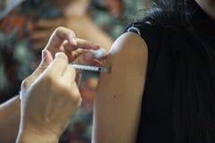 Conseguir vacunas de la gripe de un doctor con una inyección en el brazo fotos de archivo