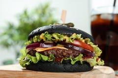 Conseil avec l'hamburger noir juteux photographie stock libre de droits