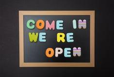 Conseil avec le cadre noir, texte entré, nous Re ouvert dans les lettres colorées, fond noir de mur photos libres de droits