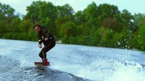 Conseil d'équitation d'homme sur des vagues Formation de cavalier d'embarquement de sillage sur le bateau de wakeboard clips vidéos