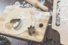 Conseil en bois avec de la farine, la pâte et les coupeurs de biscuit sous forme de coeur et mensonge o d'étoile Photo libre de droits