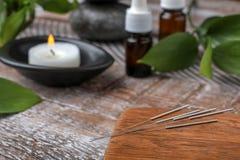 Conseil en bois avec des aiguilles pour l'acuponcture sur la table photo stock