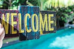 Conseil en bois avec l'accueil des textes dans la main de l'homme Île de Bali Signe bienvenu Photos libres de droits