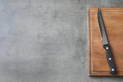 Conseil en bois avec le couteau pointu sur le fond gris, vue supérieure images stock