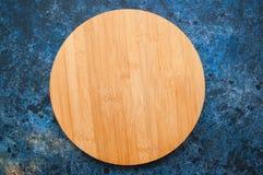 Conseil en bois vide rond sur un fond texturisé bleu Vue supérieure Photographie stock libre de droits