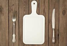Conseil, fourchette de vintage et couteau rayés Image stock