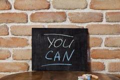 Conseil noir avec l'expression que VOUS POUVEZ vous noyer à la main sur la table en bois sur le fond de mur de briques photo libre de droits