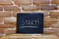Conseil noir avec le début de mot ! noyez-vous à la main sur la table en bois sur le fond de mur de briques image libre de droits
