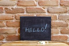 Conseil noir avec le mot BONJOUR ! noyez-vous à la main sur la table en bois sur le fond de mur de briques photographie stock