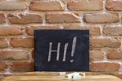 Conseil noir avec le mot HI ! noyez-vous à la main sur la table en bois sur le fond de mur de briques photo libre de droits