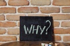 Conseil noir avec le mot POURQUOI ? noyez-vous à la main sur la table en bois sur le fond de mur de briques images stock