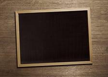 Conseil noir sur la table en bois Photos stock