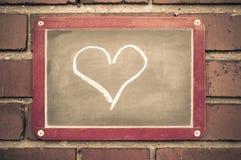 Conseil sur un mur de briques avec un coeur Photographie stock libre de droits