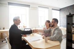 Conseiller financier de sourire de poignée de main millénaire heureuse de couples, l photos stock