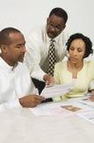 Conseiller financier expliquant des plans aux couples Image libre de droits