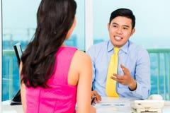 Consejero asiático con el cliente en la inversión financiera Imagen de archivo libre de regalías