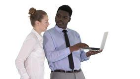 Consejero de negocio afroamericano que muestra algo en la pantalla del ordenador portátil que habla con la empresaria blanca en e almacen de metraje de vídeo
