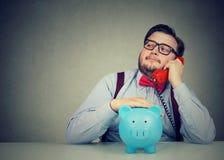 Consejero financiero con la hucha callling en el teléfono Imágenes de archivo libres de regalías