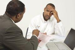 Consejero financiero en la discusión con el hombre de negocios tensado Foto de archivo