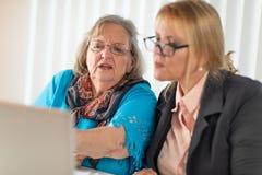 Consejero financiero que ayuda a la señora mayor en el ordenador portátil fotografía de archivo libre de regalías
