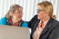 Consejero financiero que ayuda a la señora mayor en el ordenador portátil fotos de archivo libres de regalías