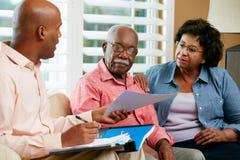Consejero financiero que habla con los pares mayores en casa Imagen de archivo libre de regalías