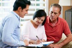 Consejero financiero que habla con los pares mayores en casa Imágenes de archivo libres de regalías