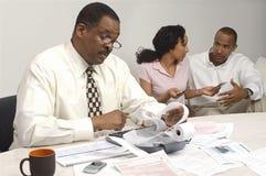 Consejero financiero que lleva a cabo el recibo del costo con los pares en el fondo Foto de archivo