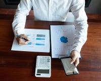 Consejo del trabajo que trabaja usando una calculadora del tel?fono imagenes de archivo