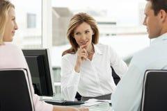 Conselheiro financeiro com pares na reunião no escritório - advogado que fornecem o conselho para equipar e mulher - mediador imo imagens de stock