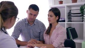 Conselho da saúde, família nova na consulta com conversa do doutor sobre a fertilidade video estoque