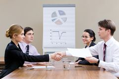 Consensus. Photo of businesspartners shaking hands after making an agreement with their co-workers looking at them stock photos