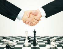 Consensus concept with men shaking hands and chess pawns. Close up Royalty Free Stock Photos