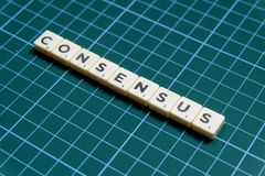 Consensus word made of square letter block on green square mat background.  stock photo