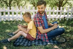 Consentrated boy is sitting back to back with his dad and playing games on phone. Dad is looking at his son and smiling. He has a phone too Stock Image