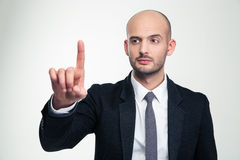 Consentrated handsome young businessman in formalwear touching copyspace with finger. Consentrated handsome young businessman in formalwear  touching copyspace Stock Photos