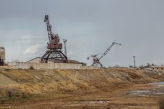 Consequences of Aral sea catastrophe. Abandoned port with rusty cranes on the shore of dried Aral sea. Consequences of Aral sea ecological catastrophe. Abandoned Stock Photo