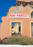Consequences of crisis. Ruins of the house to retain the sign Mini-market Stock Photos