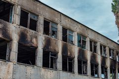 Consequences of fire. Burnt industrial or office building. Broken windows, walls in black soot.  royalty free stock image