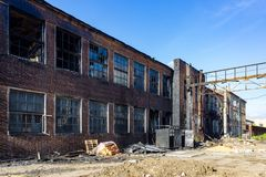 Consequences of fire. Burnt industrial or office building of red brick. Broken windows, walls in black soot.  royalty free stock photos