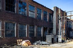 Consequences of fire. Burnt industrial or office building of red brick. Broken windows, walls in black soot.  stock photography