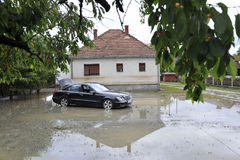 The consequences of flooding, car in front of flooded house. Stock Photos