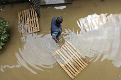 The consequences of flooding, man in the water helping neighborhood. royalty free stock image