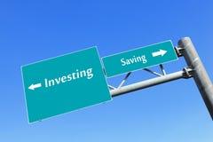 Conservando ou investindo o dinheiro no sinal de estrada Imagens de Stock