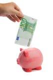 Conservando uma nota de cem euro em um piggy-banco Imagens de Stock