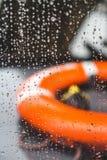 Conservante de vida alaranjado em um barco durante uma tempestade da chuva, dep raso fotos de stock royalty free