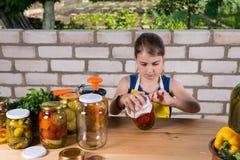 Conservas de colocação em latas da moça de legumes frescos imagem de stock