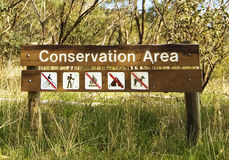 Conservation Area. A wooden sign of a conservation area in the Australian bushland. No cycling, no fire, no camping, no dogs allowed Royalty Free Stock Photos